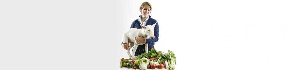 Frau hält Hund auf dem Arm vor Gemüse